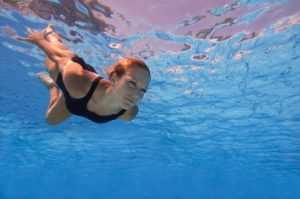 Attractive female swimming under the water surface with eyes opened. Focused on face, polarizing filter, convenient copy space